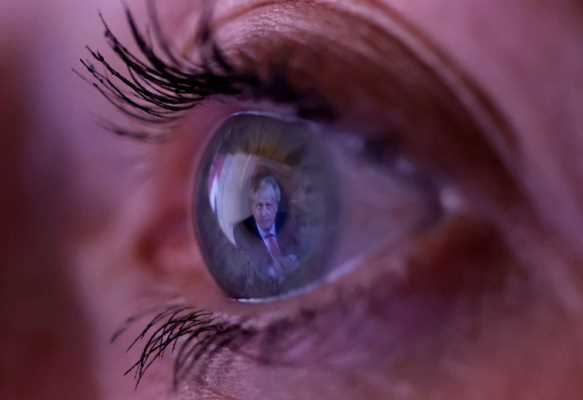 """Prime Minister Boris Johnson is reflected in a woman's eye as she watches his TV address to the nation on 22 September about a marked increase in coronavirus infections across the UK. Mr Johnson urged the public to """"summon the discipline and the resolve"""" to follow new measures, which, he said, could last up to six months.   IMAGE COPYRIGHTPHIL NOBLE / REUTERS"""